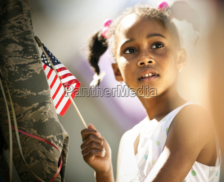 thoughtful young girl holding an american