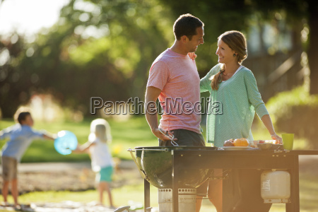 smiling couple standing by a barbecue