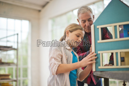 girl and her grandfather building a