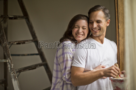 smiling young wife embraces her handsome