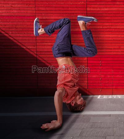 break dancer doing handstand against red