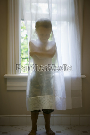 young boy standing behind a sheer
