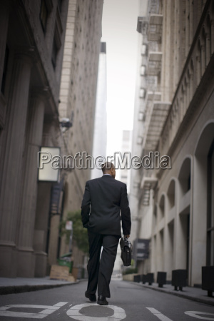 confident mid adult businessman carrying a