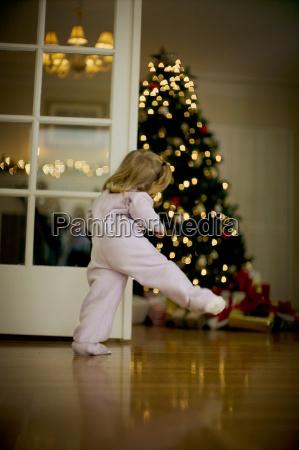 young girl peeking at presents under