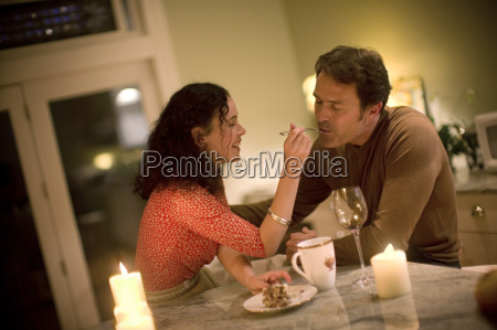 mid adult woman romantically feeding her