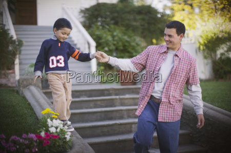 father helps son walk along ledge