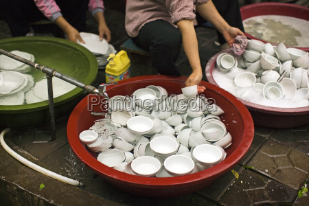 crockery being washing in tubs outside