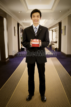young adult businessman holding a gift