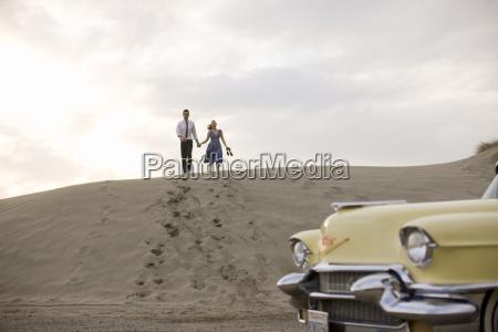 couple running down sand dune