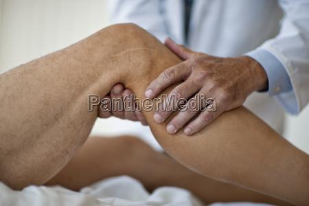 doctors hands examining a patients knee