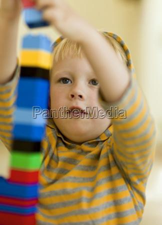 boy building a big lego stack