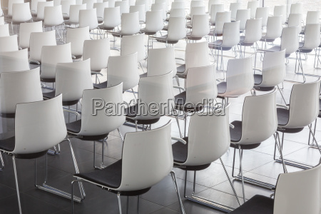 empty white chairs in contemporary conference