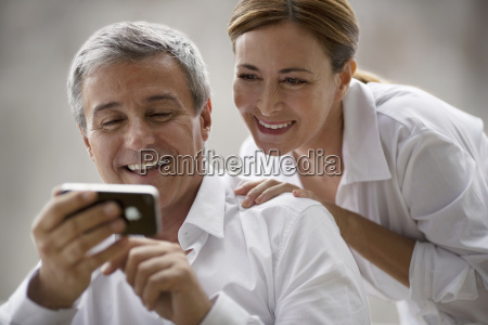 middle aged couple smile while looking