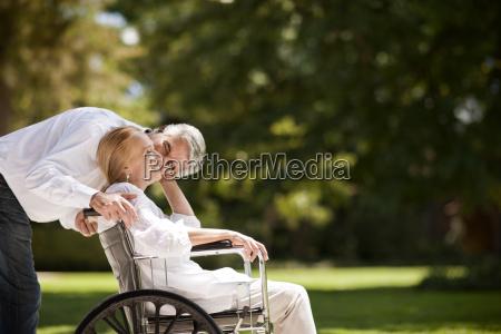 senior man pushing his wife in