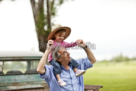mature man giving his toddler granddaughter