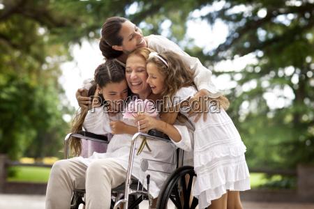 multi generational family hugging grandmother in