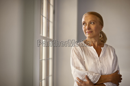 worried mature woman looking out window