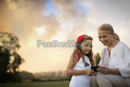 grandmother and granddaughter holding cell phone