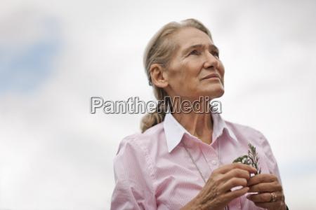 woman holding a sprig of vegetation
