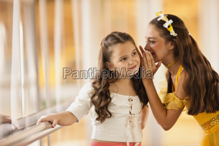 girl whispering into sisters ear