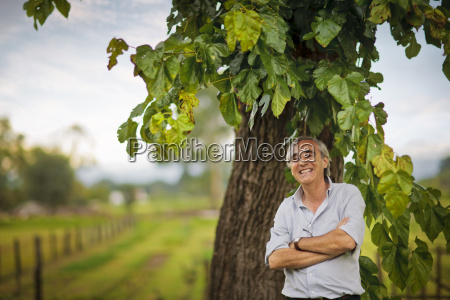 smiling farmer standing under the tree