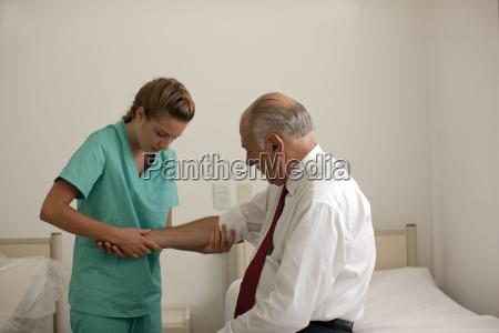 nurse examining mature mans arm