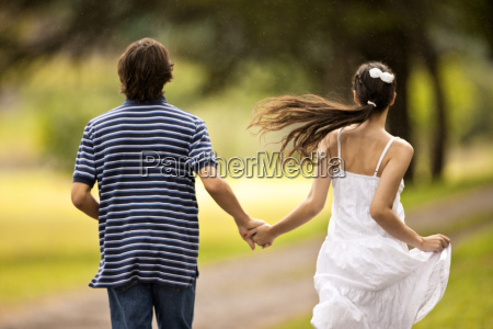 rear view of teenage couple running