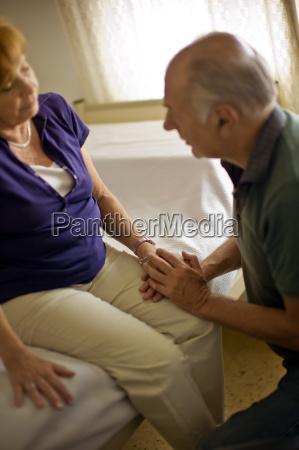 senior man reassuring his wife in