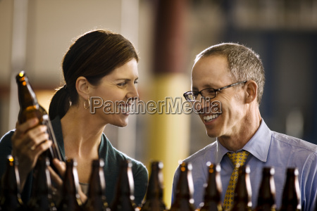 two smiling colleagues examining a row