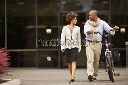 businesswoman walks with a man walking