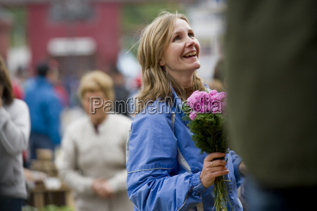 woman buying bunch of pink flowers