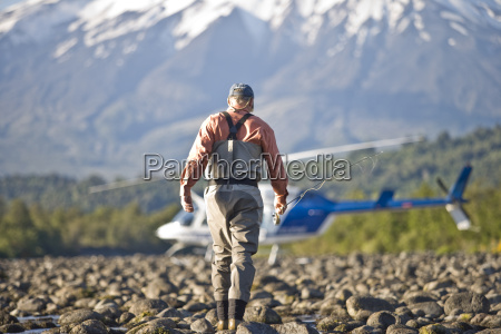 man walking towards a helicopter