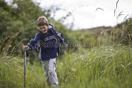 happy boy hiking through tall grass