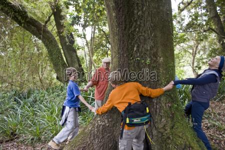 grandparents and grandchildren dancing around tree