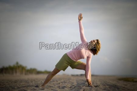 mid adult woman doing yoga on