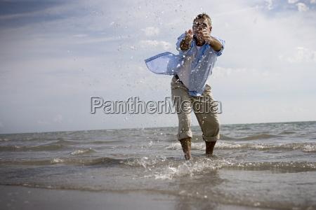 mature adult man splashing water on