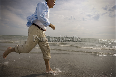 mature man running through shallow water