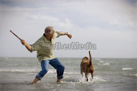mature adult man throwing a stick