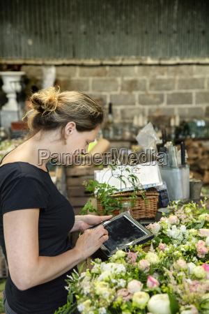 a woman florist using a digital