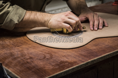 luthier manufacturing a guitar in his