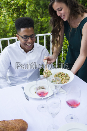 woman serving tabbouleh to her guest