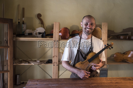 smiling luthier holding a violin in