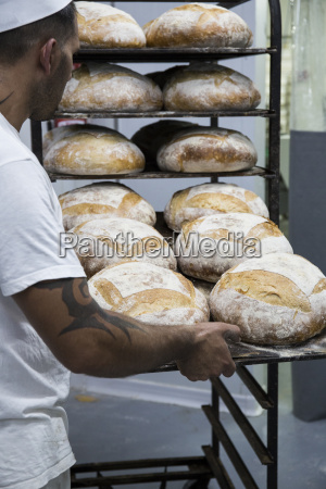 baker placing a tray of bread