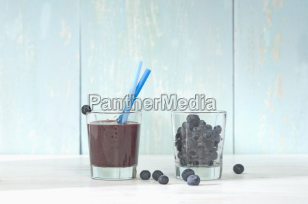 blueberry smoothie in glass with drinking