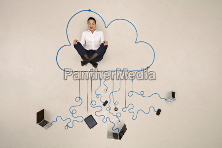 businesswoman meditating in a cloud connected