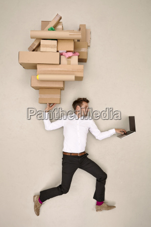 businessman balancing cardboard boxes and working