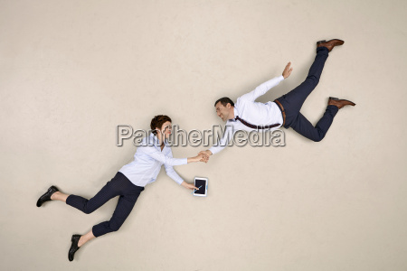 two bussiness colleagues flying and shaking