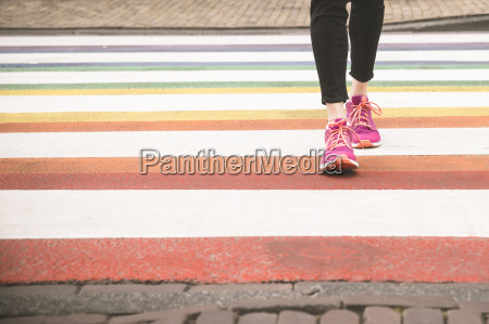 woman crossing multi coloured zebra crossing