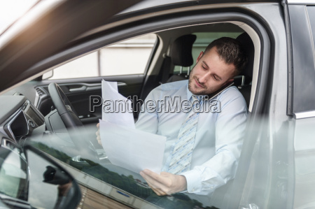 businessman with documents on cell phone