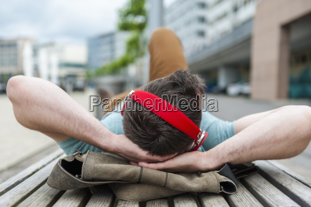 relaxed young man lying on bench
